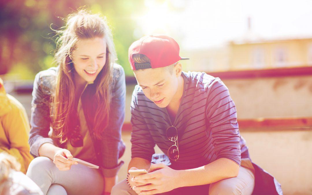 kaksi onnellista teiniä ulkona matkapuhelinten kanssa